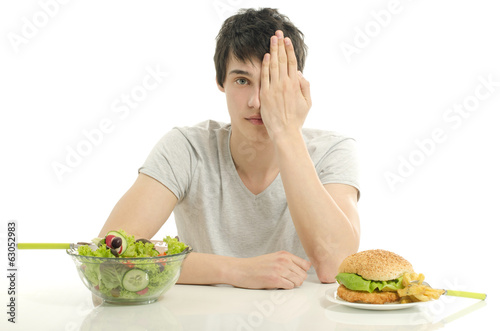 Man holding in front a bowl of salad and a big hamburger