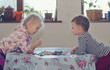 Young boy and girl playing checkers