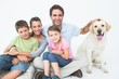 Cute family with pet labrador posing and smiling at camera