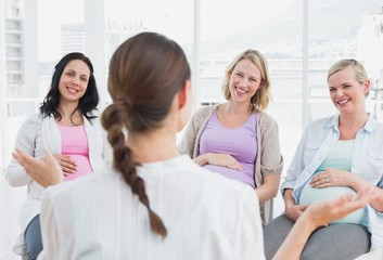 Pregnant women listening to doctor at antenatal class