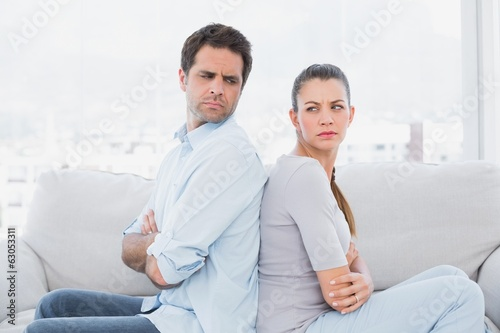 Angry couple sitting back to back on the couch