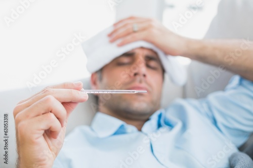 Sick man lying on sofa checking his temperature