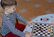 Little boy setting up a game of checkers