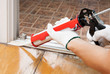 Worker applies silicone caulk on the wooden floor for sealant wa - 63053536