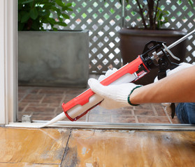 Carpenter applies silicone caulk on the wooden floor for sealing