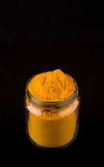 Powdered tumeric spices over black background
