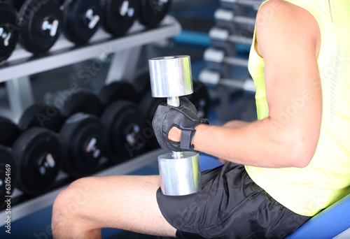 Guy with dumbbells on gym background close-up