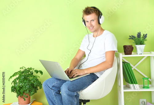 Young man relaxing with laptop in armchair,