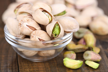 Pistachio nuts in glass bowl on wooden background