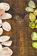 Peeled pistachios nuts on wooden background