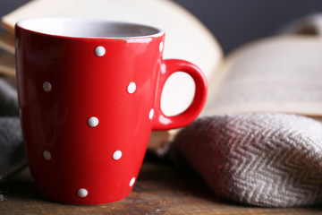 Cup of hot tea with book and plaid on table close up