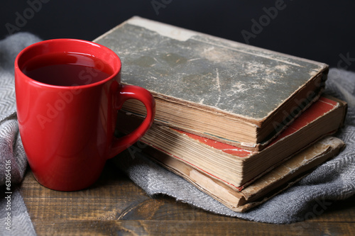 Cup of hot tea with books and plaid on table close up