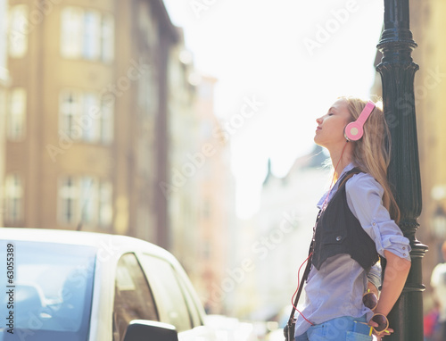 Relaxed young woman listening music in headphones in the city