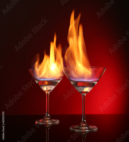 Glasses with burning alcohol on red background