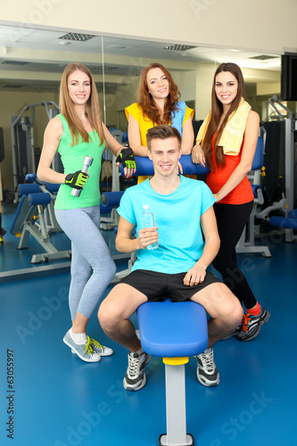 Group of people relaxing after training in gym