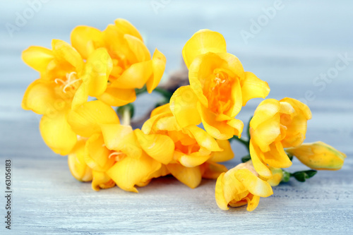 Beautiful freesias on wooden table
