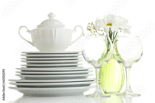Stack of white ceramic dishes and flowers, isolated on white
