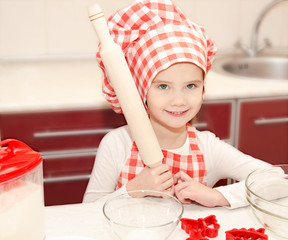 Smiling little girl with chef hat preparing to cook