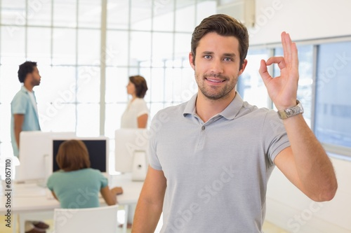 Businessman gesturing ok sign with colleagues in meeting