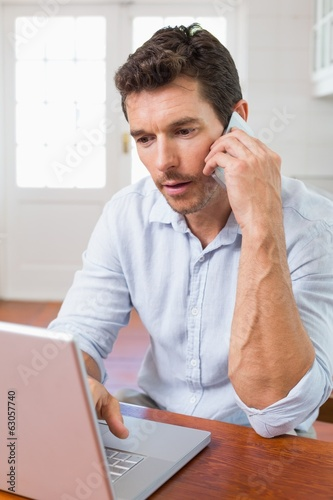 Concentrated man using laptop and mobile phone