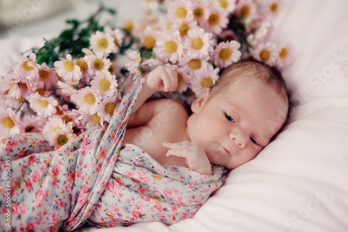 little baby wrapped in a blanket color and bouquet of flowers