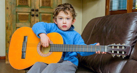 baby boy play guitar on sofa