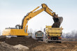 Digger loading trucks with soil - 63060590