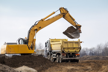 Digger loading trucks with soil