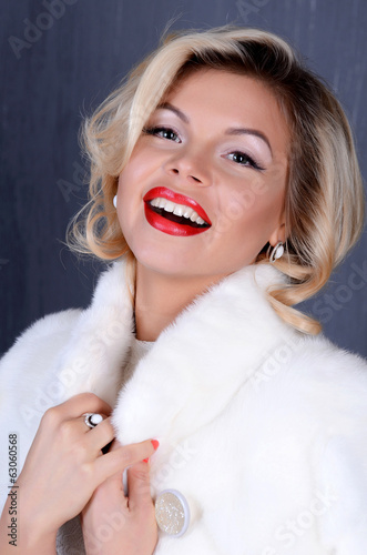Beautiful sensual woman in to a white fur coat