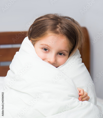 Girl sitting on the bed wrapped in a blanket