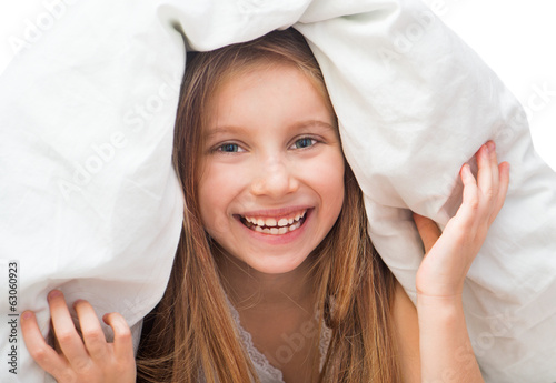 Laughing little girl under a blanket