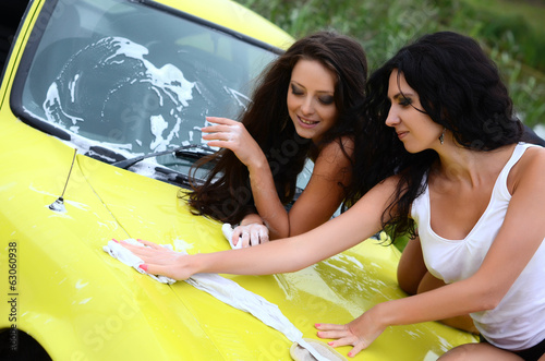 The beautiful woman washes the car