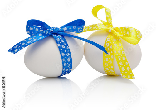 Two Easter eggs with festive blue and yellow bow isolated on whi