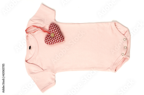 Close up of an pink baby onesie with a smal red heart on it