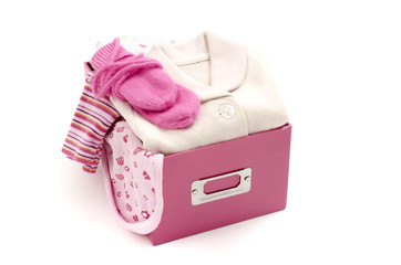 Close up of a box full with baby pink clean clothes isolated