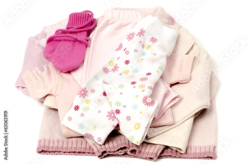 Close up with a pink stack of clean baby clothes isolated