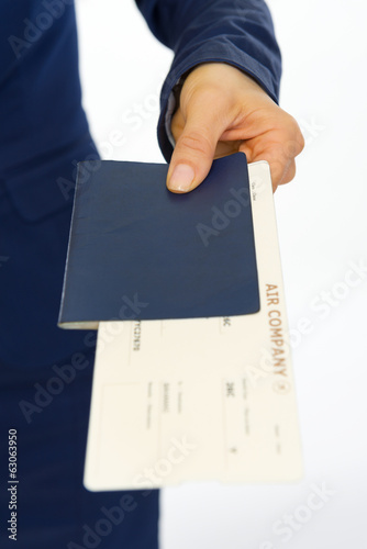 Closeup on business woman giving passport and ticket