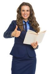 Happy business woman with book showing thumbs up