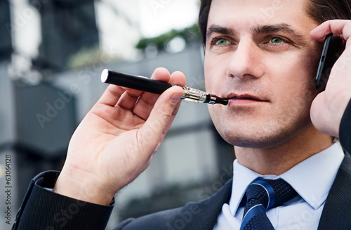 Businessman is smoking electronic cigarette outdoor