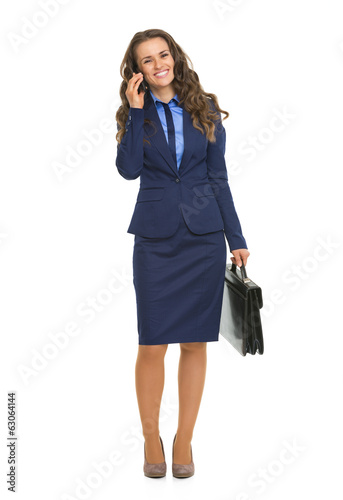 Full length portrait of business woman talking mobile phone