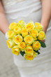Wedding bouquet with many yellow roses in hands of bride