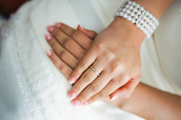 bride holding hands on a white wedding dress