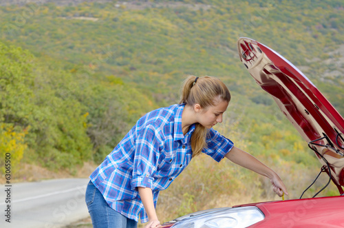 Young woman near broken car