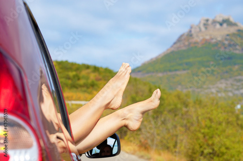 Female feet stick out of car window