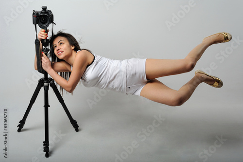 Photographer woman flaying with camera - levitation