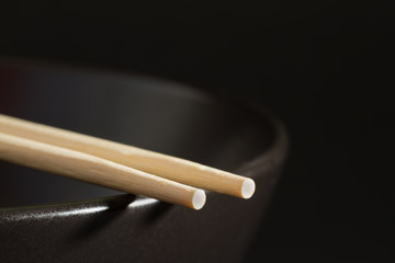 Two chopsticks on a black bowl