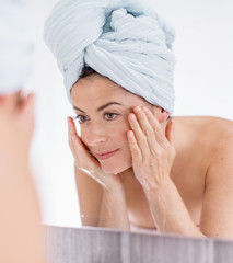 Mature lady using soap and water to purify her skin