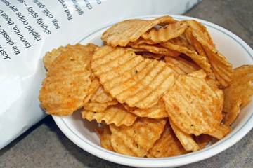 A bowl of spicy barbecued rippled potato chips beside bag