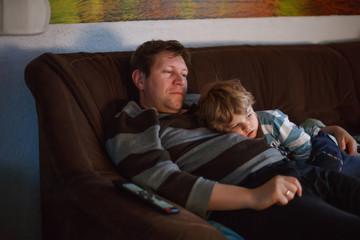 Cute little boy and his father watching tv