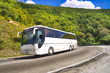 Tourist bus traveling on road among mountains - 63068553